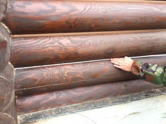 Укладка теплоизолирующего шнура между бревен для теплого шва